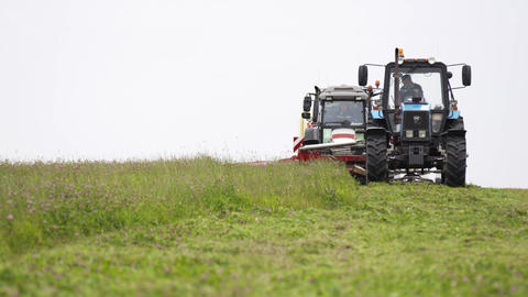 Line of agriculture tractors riding on grass field at farm Live Action