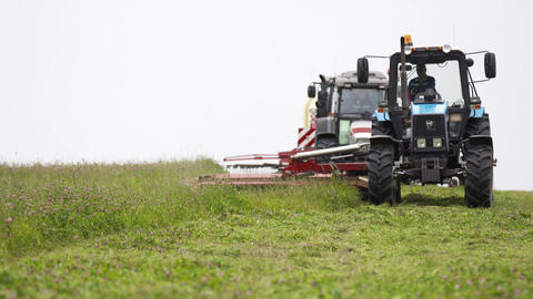 Line of agriculture machines cutting on grass field at farm Footage