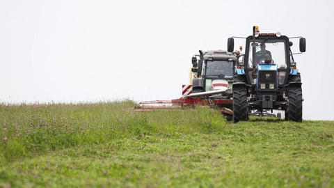 Line of agriculture tractors driving on grass field at farm Footage