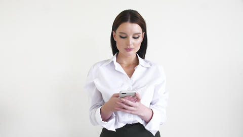 Beautiful business woman in is typing sms on the smartphone at backdrop of white Live Action