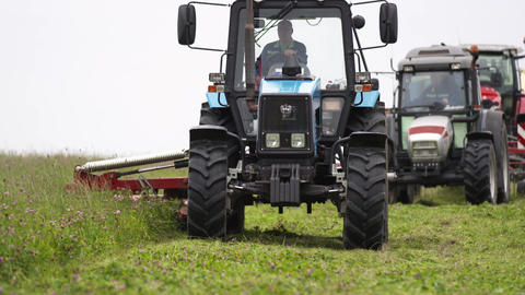 Line of agriculture machines cutting on grass margin at farm Live Action