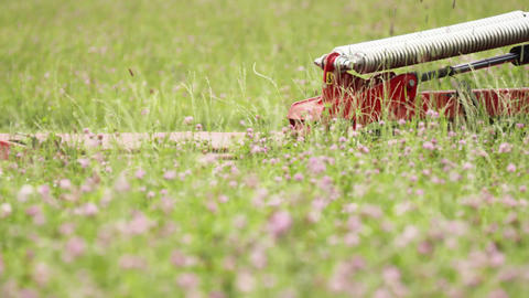 Agriculture red machine gather green grass on clover field Footage
