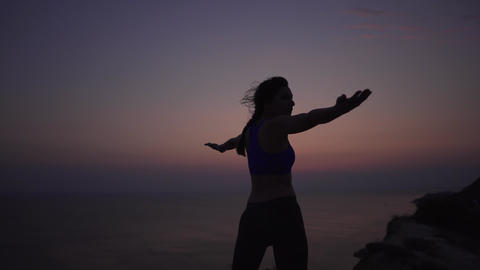 A girl practices yoga until the dawn of the sun by the ocean in the mountains Footage