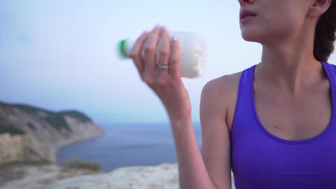 The sports girl shakes a white bottle with a protein shake after training on the Footage