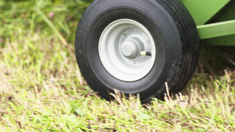 Black rubber wheels of agricultural combine harvester machine riding on grass Footage