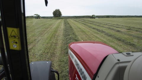 View from agriculture tractor cabin driving at farm grass field Footage
