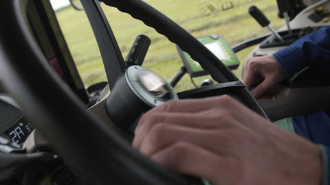 Hands of driver on steering wheel of tractor riding on farm field Footage