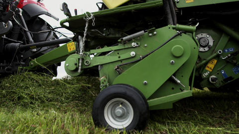 Combine harvester machine carriage collects cutted grass on farm margin Live Action