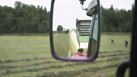 View on rear mirror from agriculture tractor cabin driving at farm grass margine Live Action