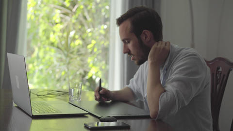 Handsome skill bearded man draws using graphic tablet looking into a laptop Live Action