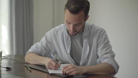 Man sitting at the table writing something on the paper at home. Profession Footage