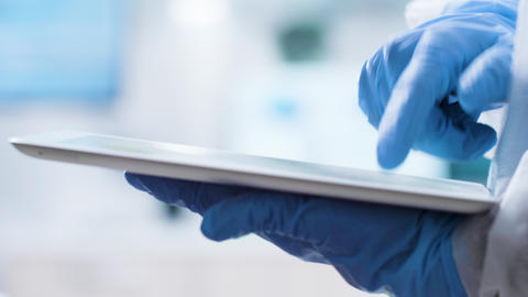 Close up shot of scientist in gloves typing on a tablet PC screen Live Action