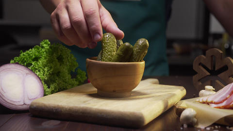 Slide zooming shot: chef takes pickle from the bowl on the kitchen table, canned Footage