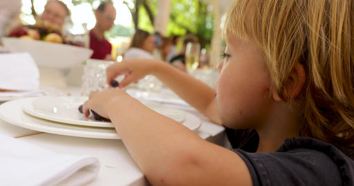 Curios kid eating grapes at table in outside restaurant Footage