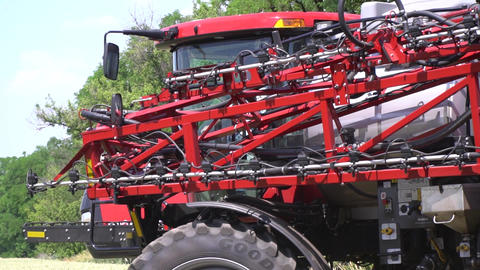A huge self propelled sprayer is driving on the field on a sunny day Live Action