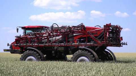 Agricultural machinery, self propelled sprayer is driving on a green field Live Action