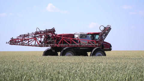 Big red self propelled sprayer is unfolding its arms before spraying Live Action