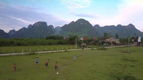 active boys play football on green field near small village Footage
