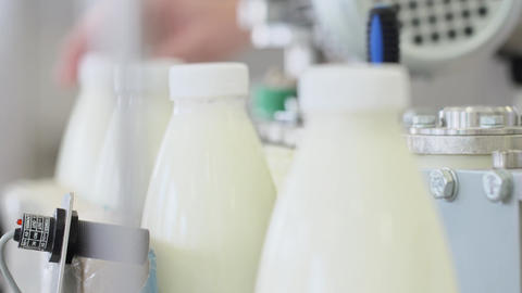 Machine at milk production line. Packing bottles. Bottle label at dairy plant Footage