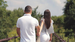 Couple in love having fun in park. Smiling woman leading man hand in park at Footage