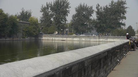 fishing by sparkling moat lake relying on fence in Beijing Forbidden City Footage