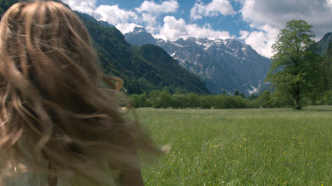 Mid shot - Young woman in a white dress running through the meadow Footage