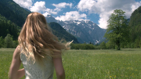 Mid shot - Happy young woman in a white dress running through the meadow Footage