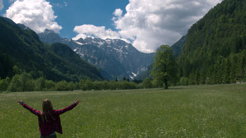 Happy woman with outstretched arms standing in the meadow Footage