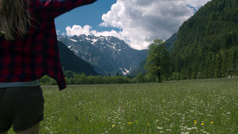 Back view of a woman standing in the meadow and raising arms Live Action