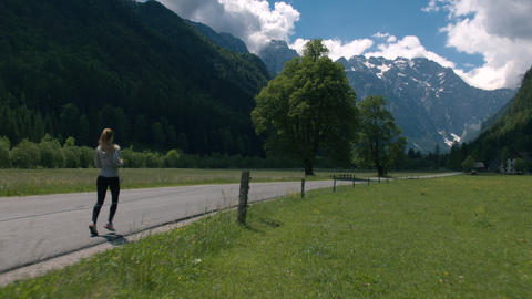 Young woman jogging on scenic rural road Footage