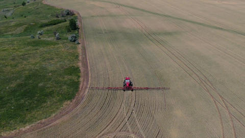 Aerial footage of a self propelled sprayer driving through the wheat field Live Action