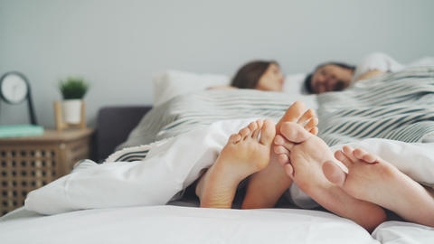 Man and woman lying in bed touching feet talking enjoying bedtime together Footage