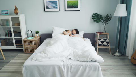 Zoom in of man and woman hugging talking rubbing noses kissing in bed Live Action