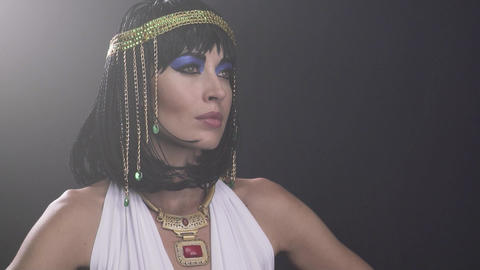 Close up of legendary Cleopatra with lots of jewelry and a smirk on her face Live Action