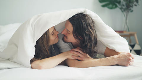Happy couple kissing rubbing noses under blanket lying on bed at home together Live Action