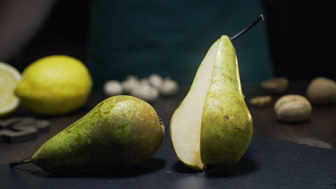 Slide zooming shot: chef takes piece of raw juicy pear, fresh fruit, ingredients Live Action