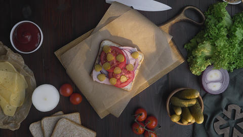 Flat lay of making the sandwich with sliced bacon, pickle and vegetables on the Footage