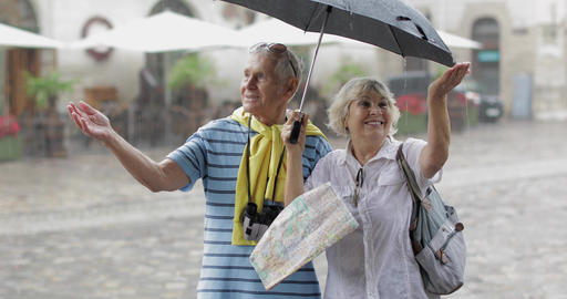 Happy senior tourists stand downtown and enjoy the rainy weather in Lviv Live Action