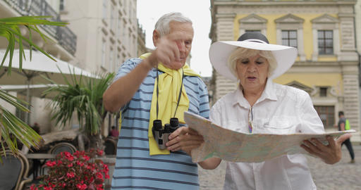 Senior two tourists having discussion about planning tourist route in Lviv Footage
