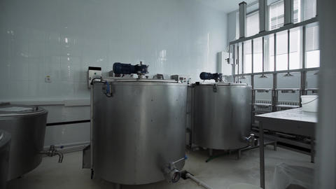 Dairy factory equipment. Cylindrical tanks with pipes and hoses at factory Footage
