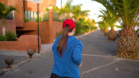 Woman runs down the street among the palm trees at sunset, back view. Healthy Footage