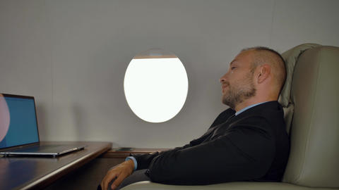 Rich entrepreneur work on notebook inside of private jet Live Action