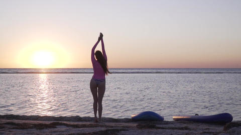 Slim young woman is dancing on the beach at sunset Live Action