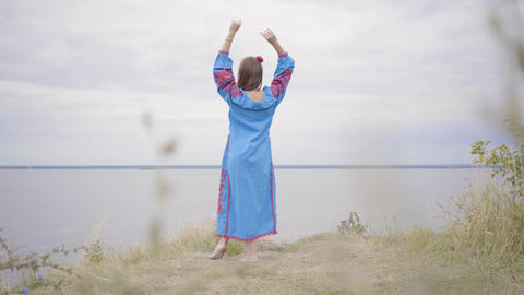 Rear view at carefree caucasian young woman wearing long summer fashion dress Footage