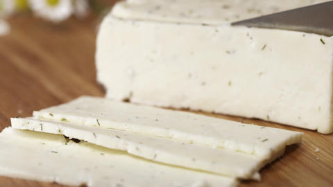 Tasty white cottage cheeze with herbs being cutted with blade on cutting board Footage