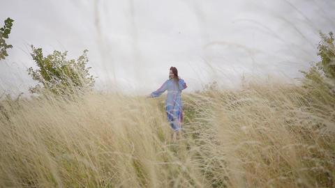 Beautiful carefree caucasian girl wearing long summer fashion dress walking on Footage