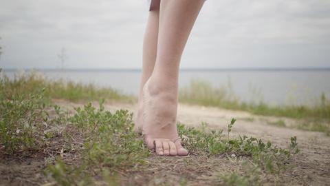 Beautiful carefree barefoot girl wearing long summer fashion dress looking Footage