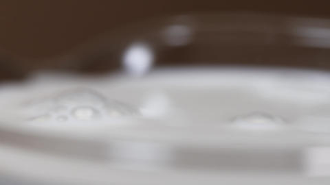 Tear of pure milk falls into glass making ripple on surface Footage