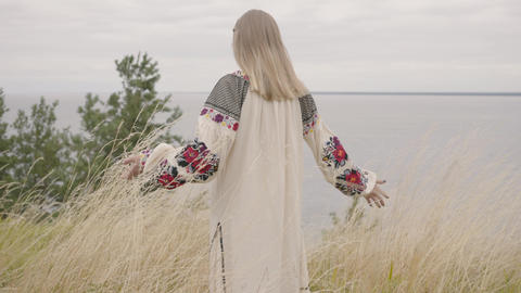 Rear view at awe caucasian woman wearing long summer fashion dress standing on Live Action