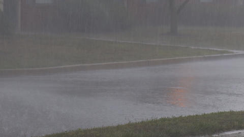Heavy rain splashes the road in a residential area a thunderstorm Live Action